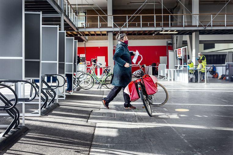 Er kan nu al gestemd worden in de RAI. Het gehannes met fietsen en mondkapjes ziet er inmiddels herkenbaar Amsterdams uit.   Beeld Jean-Pierre Jans
