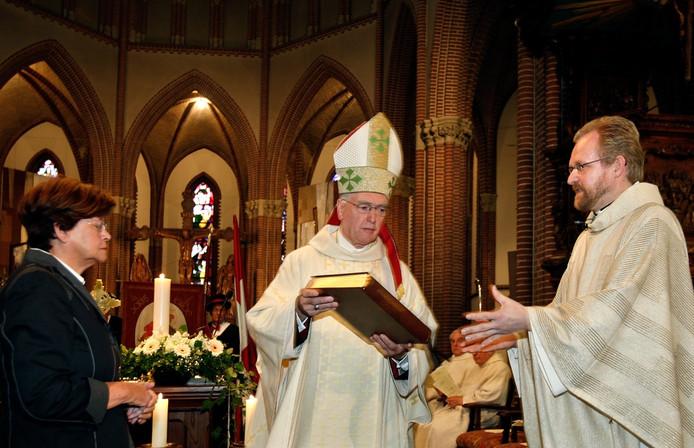 Archieffoto: Tijdens zijn installatie kreeg de nieuwe pastoor Jos Hermans (rechts) onder andere het evangelieboek overhandigd. Op de foto wordt het hem aangereikt door bisschop Hurkmans.