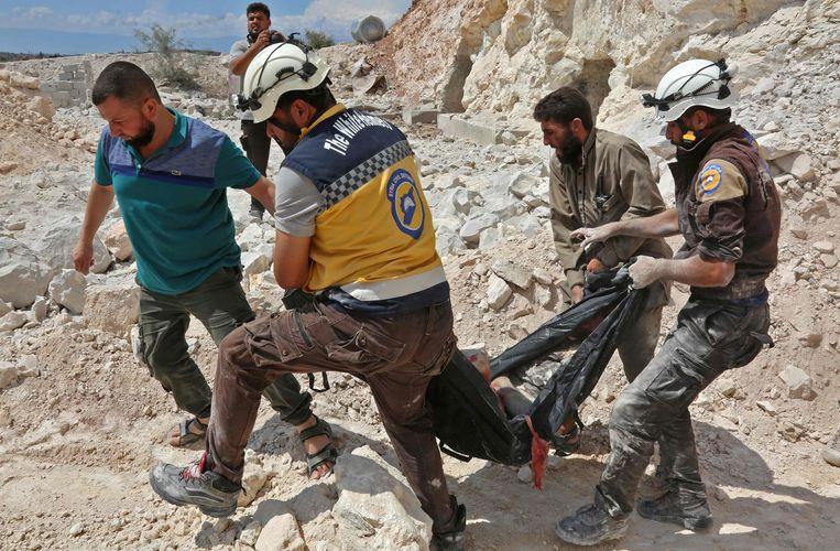 Leden van de Witte Helmen ruimen lijken na aanvallen in Idlib.  Beeld AFP