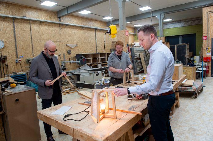 Steef Niesing (rechts) en Bernd Teule (links) hebben een circulaire lamp ontworpen, gemaakt van lokaal afval. In het midden  Sander Korevaar, die de lampen in elkaar zet.