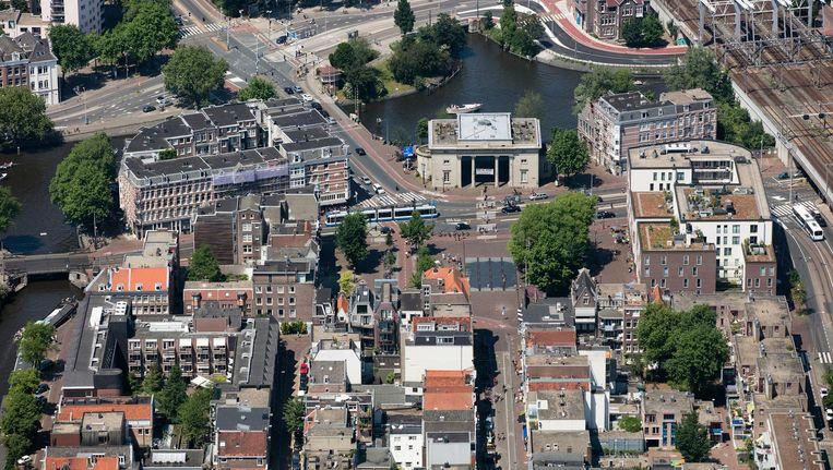 De Haarlemmerpoort/Willemspoort aan het Haarlemmerplein. Onder in het midden de Haarlemmerdijk, met links de Vinkenstraat en de Brouwersgracht, en rechts de Haarlemmer Houttuinen en de spoordijk in de richting Haarlem/Zaandam. Het water achter de poort is het einde van het Westerkanaal, daarboven begint het Westerpark. Beeld Peter Elenbaas