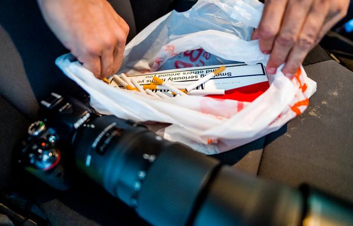 Een privédetective die werkt voor Philip Morris toont een slof namaaksigaretten die hij net op de kop heeft getikt bij een Haagse supermarkt.