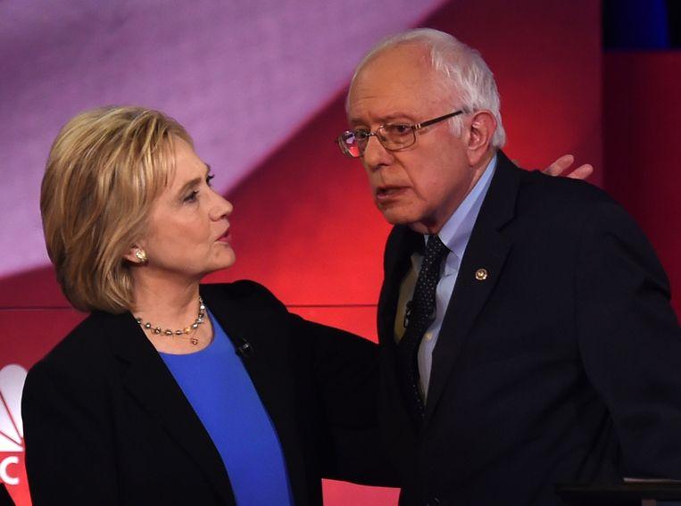 Clinton en Sanders zondag in het laatste Democratische debat voor de stemming in Iowa. Tot verbazing van Sanders, werden de vier Democratische debatten gehouden op tijdstippen waarop tv-kijkers vooral naar sportwedstrijden kijken. Beeld AFP