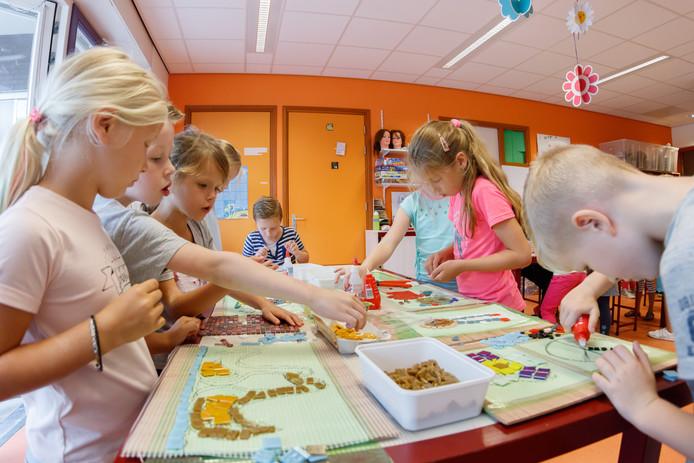 Een van de klaslokalen op de Arenbergschool is omgetoverd tot een ware mozaïekfabriek.