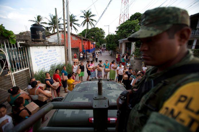 Een Mexicaanse soldaat kijkt naar huisvrouwen die in de rij staan voor rantsoenen en water in Juchitan in de deelstaat Oaxaca, die het zwaarst werd getroffen door de aardbeving.
