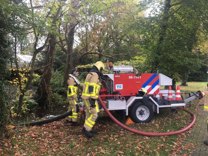 De brandweer pompt water uit de Klarenbeek bij de brand bij Krepel.