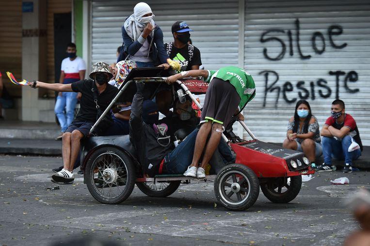 Jongeren in een zelfgemaakte auto in de arme wijk Siloe in Cali, het centrum van de protesten tegen de regering.  Beeld  Luis Robayo / AFP