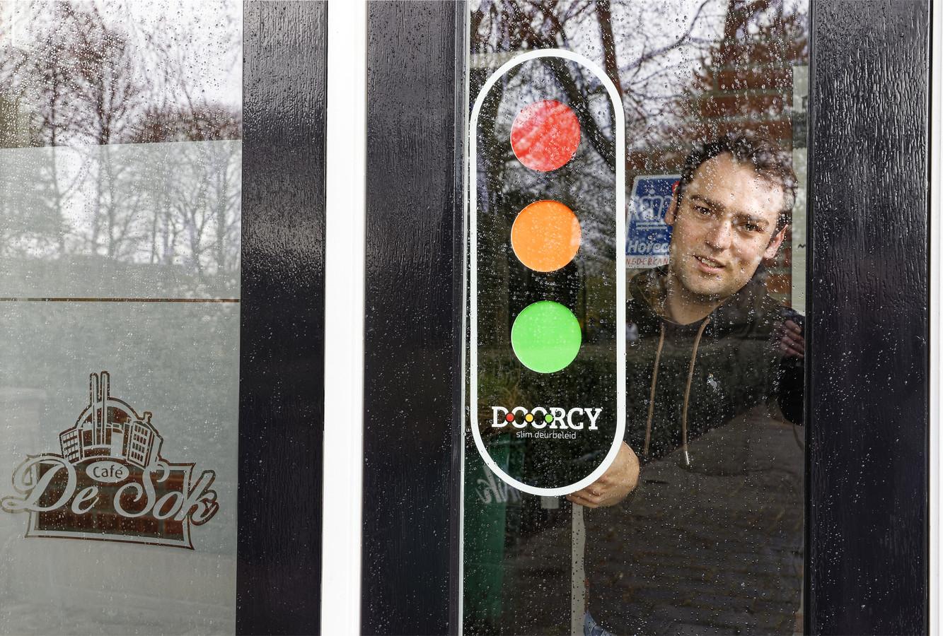 Thomas de Groot plakt een slim stoplicht op de voordeur bij zijn café De Sok in Schijndel.