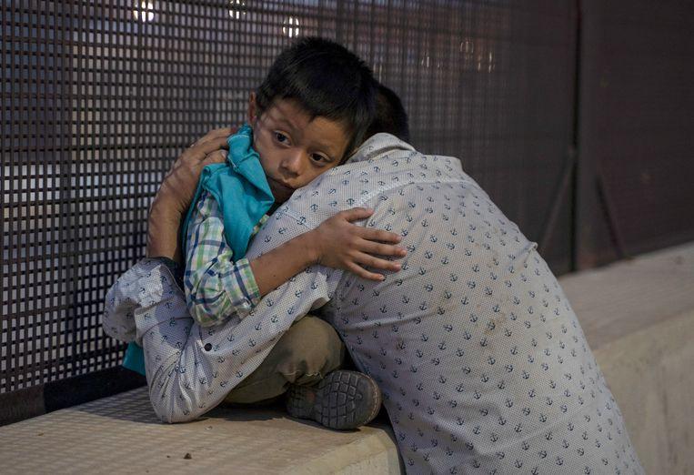 Vader met zoon op de grens van Mexico en de Verenigde Staten.  Beeld AFP