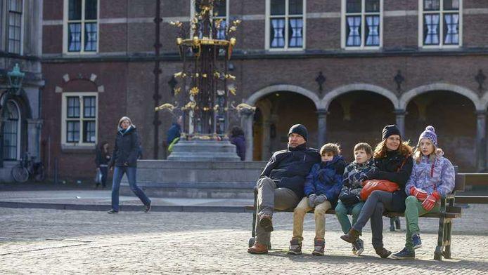 Toeristen zitten op een bankje in de zon op het Binnenhof tijdens de krokusvakantie.