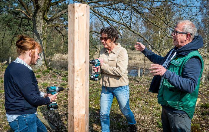 Oud-boswachter Jap Smits geeft tips aan Bijenkorf-medewerksters Mariëtte de Bont (l) en Karin Roggeband bij het maken van een bijenhotel op de Strabrechtse Heide in Heeze.