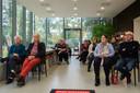 De Corona in Tilburg-docu gaat in première in het Peerke Donders Paviljoen voor een aantal mensen die een rol spelen in de film. Aandachtig bekijkt men de film.