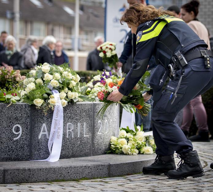 Een agente legt bloemen bij de gedenkplek voor de slachtoffers van het schietdrama in 2011 in het Alphense winkelcentrum Ridderhof.