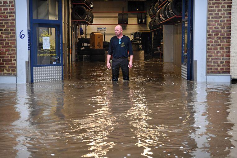 Een Mechelse garagehouder ziet hoe het water zijn zaak binnenstroomt. Beeld Marcel van den Bergh / de Volkskrant