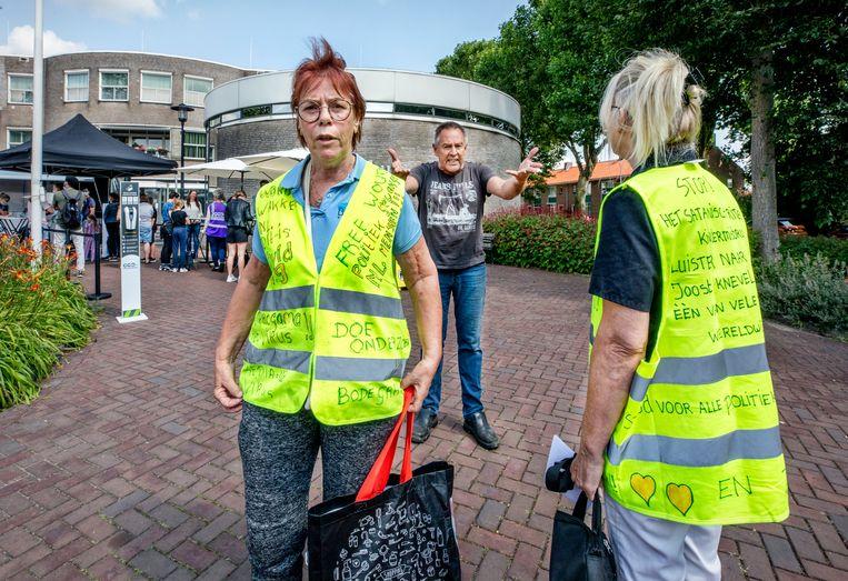 Confrontatie tussen een man die voor vaccinatie is (midden) en tegenstanders in gele hesjes, die werden geweerd bij de vaccinatiebus voor het gemeentehuis in Lekkerkerk.  Beeld Raymond Rutting / de Volkskrant