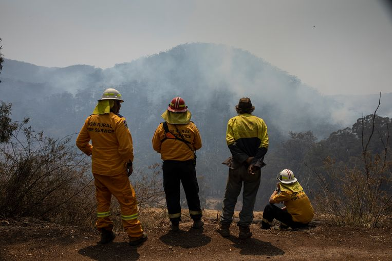 Lokale brandweerlieden kijken uit over de vallei waar bosbranden woeden.   Beeld David Maurice Smith/Oculi