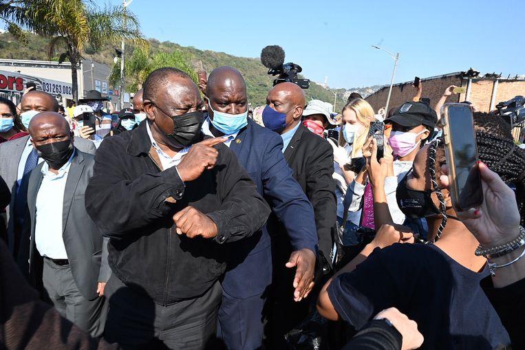President Cyril Ramaphosa (vooraan) bezoekt geplunderde plaatsen, hier is hij in Durban. Slaagt hij erin het land onder controle te houden? Beeld EPA