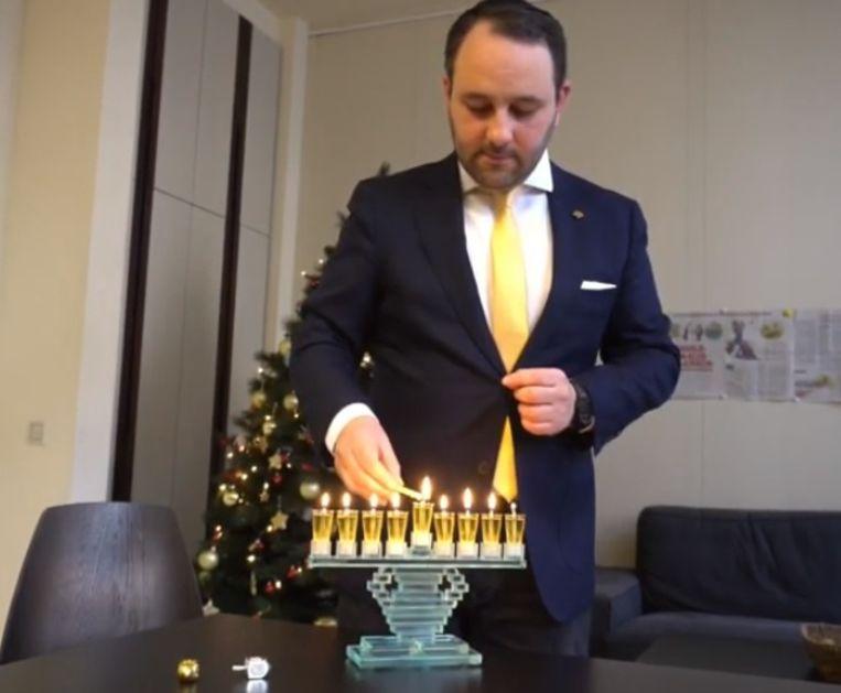 N-VA-parlementslid Michael Freilich steekt een joodse kandelaar aan in de Kamer. Beeld Screenshot YouTube