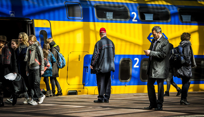 Een conducteur staat bij een NS-trein op station Rotterdam Centraal.