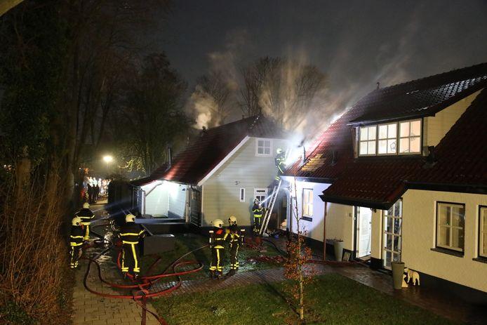 De brand in de woning aan de Voorstraat in Almkerk. Er komt veel rook vrij.