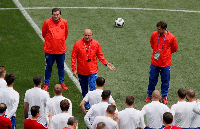 De Russische bondscoach Stanislav Tjertsjesov (kale man in het rood) spreekt zijn ploeg toe. Beeld Reuters