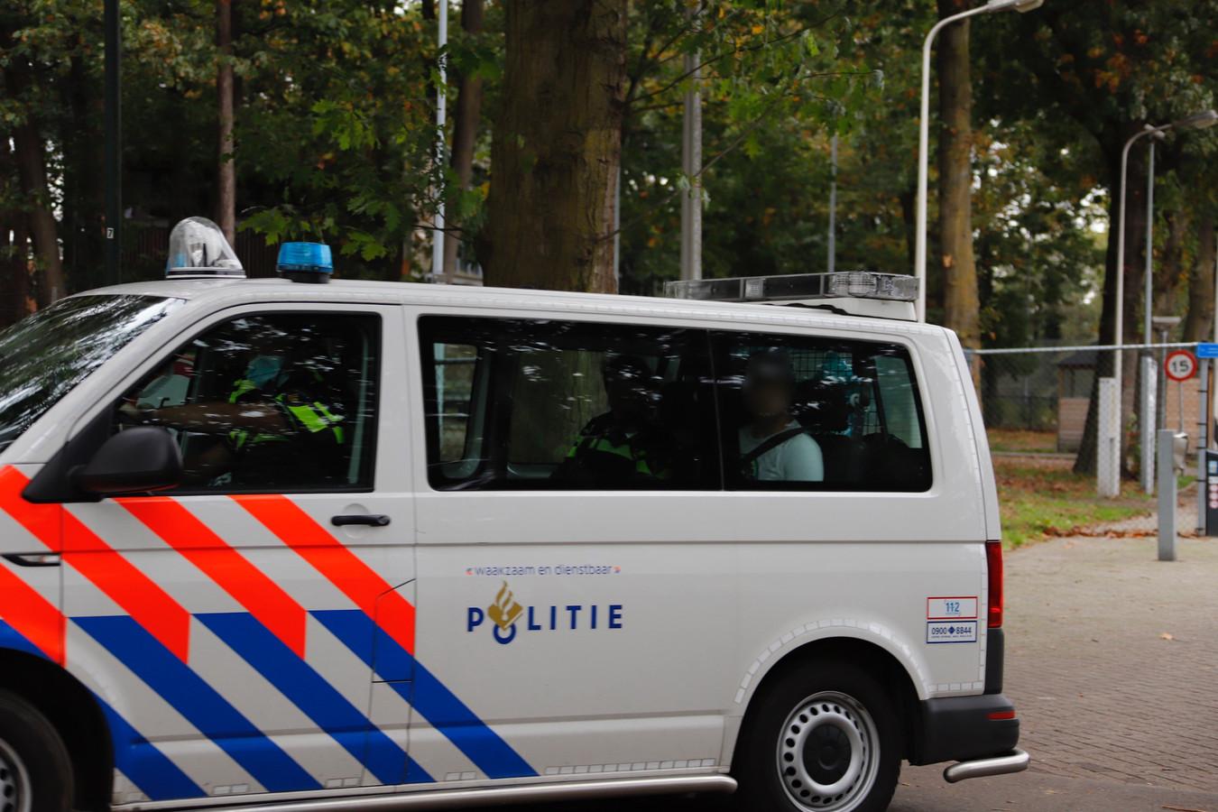 De bewoner van het asielzoekerscentrum in Overloon wordt door de politie naar de arrestantencel vervoerd nadat hij agressief was geworden en een ruit had ingeslagen.