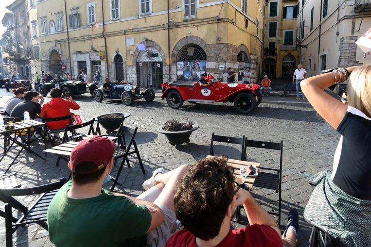 Terrasbezoekers kijken naar passerende klassiekers tijdens de beroemde Mille Miglia classic race in Italië.  Beeld EPA