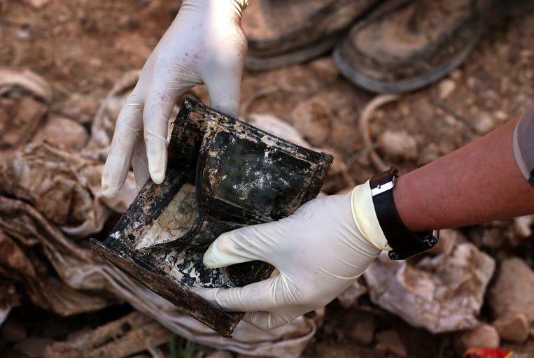 Een Irakese ambtenaar onderzoekt een portefeuille die in een massagraf werd gevonden. Beeld AFP