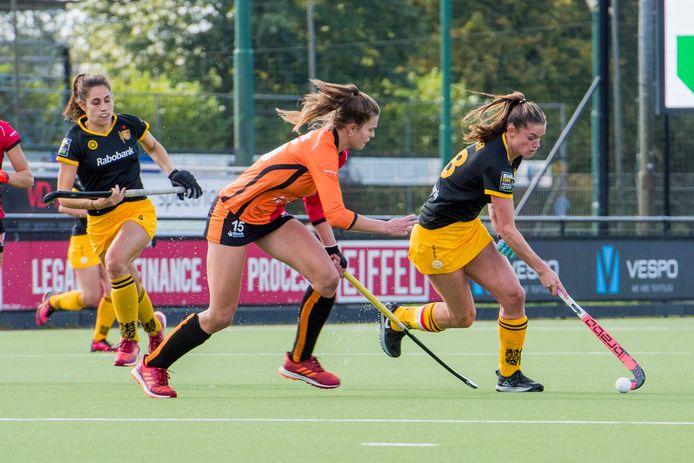 Lidewij Welten (aan de bal namens HC Den Bosch) en Kim Janssens van Oranje-Rood.