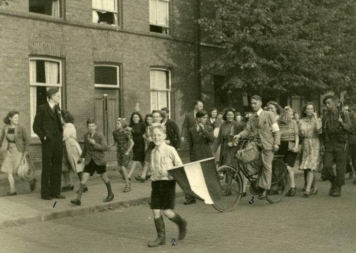 Na de bevrijding van Oss in september 1944 gaat de bevolking uitgelaten de straat op. Voorop met vlag het jongere broertje van fotograaf Leo van den Bergh.