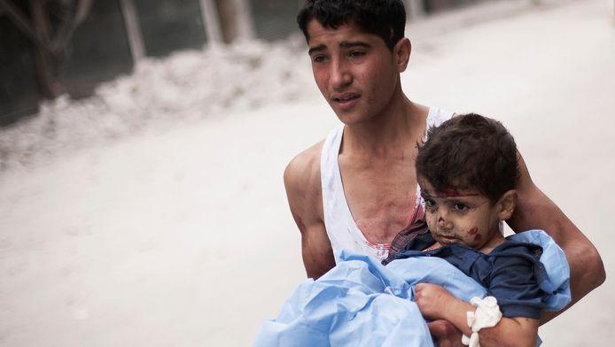 Een Syrische jongen met een gewond kind op de arm na een aanval van het Syrische leger in Aleppo.