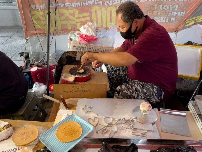 Sur cette photo prise à Séoul le 10 octobre 2021, le vendeur ambulant Lim Chang-joo fabrique un dalgona, un biscuit présenté dans la série à succès de Netflix Squid Game, pour laquelle lui et sa femme, Jung Jung-soon, ont été engagés sur le plateau pour le fabriquer pendant la production.