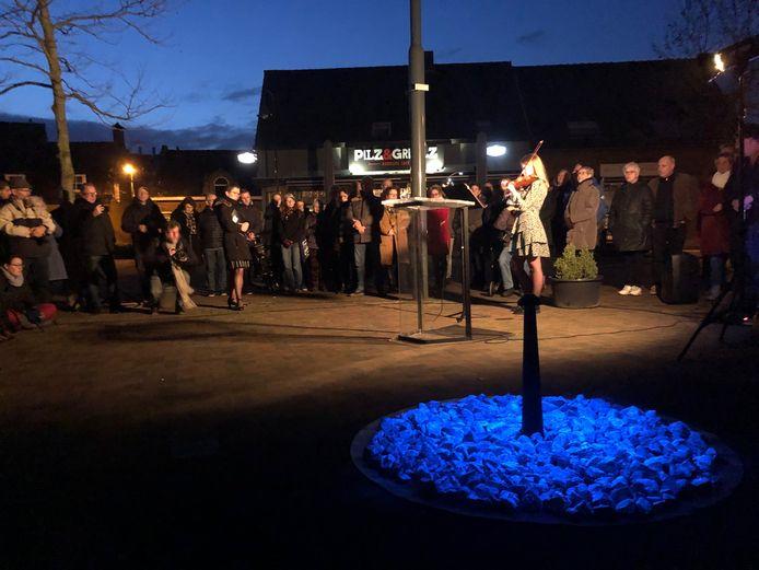 De herdenking in Veghel werd opgeluisterd met vioolmuziek. Op de voorgrond het kunstwerk met de oplichtende steentjes.