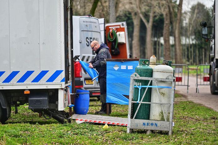 Grote IBC bulkcontainers worden uit het drugslab in Wernhout gehaald.