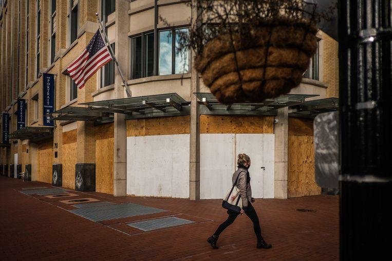 Een vrouw passeert een winkel in Washington die, uit vrees voor gewelddadige protesten na de presidentsverkiezingen, gebarricadeerd is met houten panelen. Beeld EPA