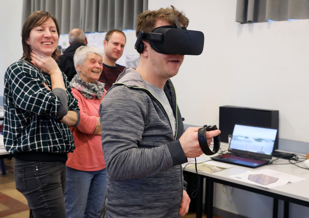 """Joren Robyn uit Melsele """"wandelt"""" door middel van virtual reality door Grenspark Groot-Saeftinghe. Katrien Weyn (links) begeleidt de belangstellenden in de computerwereld."""