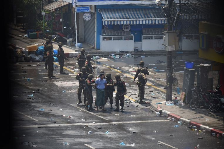 Militairen arresteren een betoger in Yangon. De foto is vanachter een raam gemaakt. Beeld REUTERS
