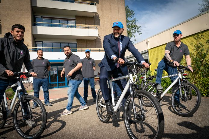 Burgemeester Ahmed Marcouch wenst de nieuwe straatcoaches van Presikhaaf en Malburgen succes en probeert zelf even de fiets uit waarop ze rijden. Derde van links straatcoach Mimoun Ahbouk.