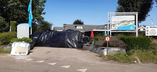 De ingang van recreatiepark Het Esmeer is dichtgemaakt met grote zandzakken en plastic.