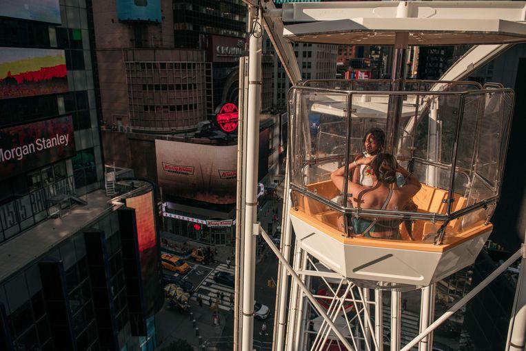 Bezoekers bewonderen het uitzicht op Times Square vanuit een reuzenrad. New York City stelt iedere dag honderd gratis kaartjes voor de attractie beschikbaar aan inwoners die zich laten vaccineren tegen Covid-19. Beeld AFP