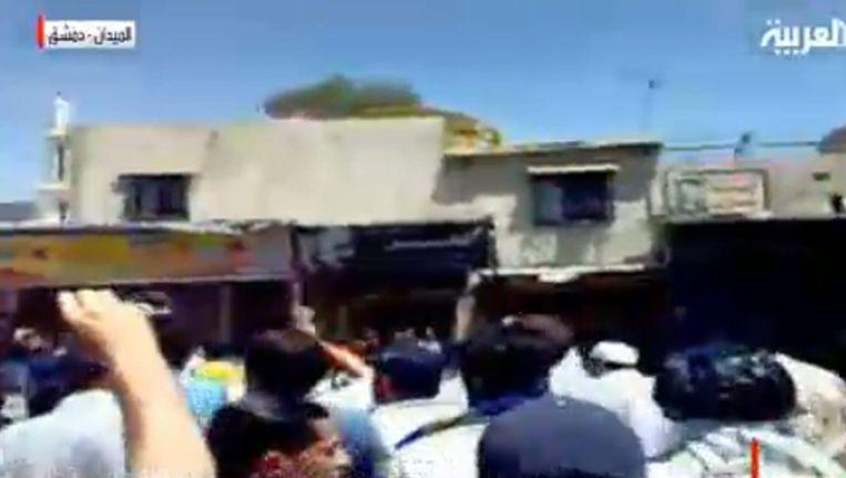 Een televisiebeeld van demonstranten in Damascus. Beeld epa