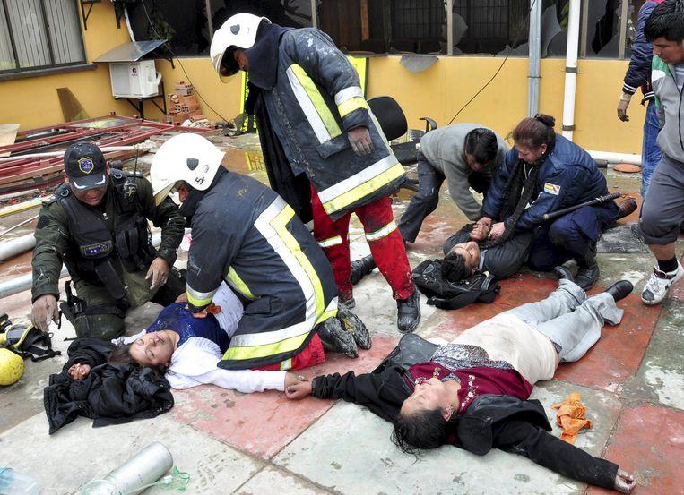 Gewonde personeelsleden die werkzaam waren in het gebouw krijgen verzorging. Beeld REUTERS