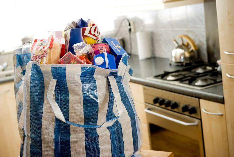 Een tas boodschappen aannemen kan tot terugvordering van bijstand leiden. Steeds meer gemeenten willen hiervan af en kiezen ervoor 1200 euro per jaar aan giften vrij te stellen. Beeld ANP XTRA Lex van Lieshout