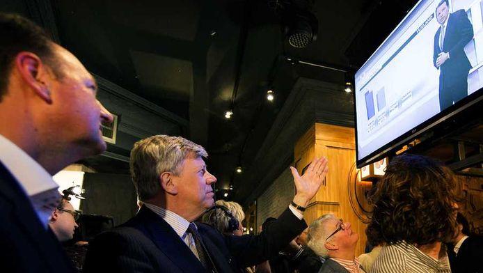 VVD-minister Ivo Opstelten (2e L) wacht in een café in Breda de uitslagen van de verkiezingen af