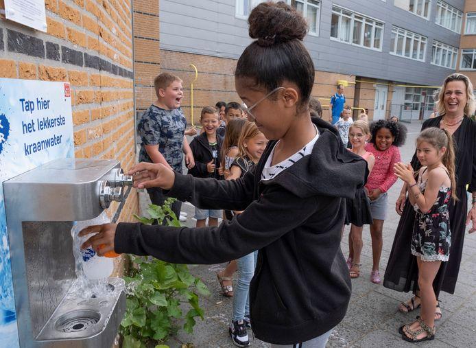 Diyoli (13) tapt als eerste een fles water uit het nieuwe watertappunt op het schoolplein van De Stroming.