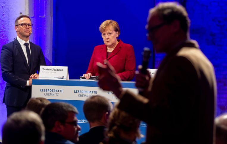 Bondskanselier Angela Merkel op een debat van de krant 'Freie Presse' tijdens haar bezoek aan Chemnitz. Aan haar zijde: hoofdredacteur Torsten Kleditzsch. Beeld EPA