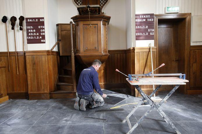 Tegelzetter bezig in hervormde kerk Heteren.