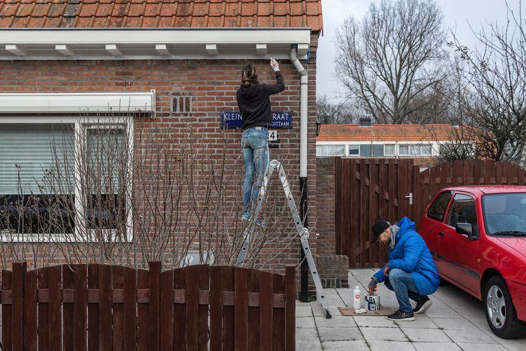 Nieuwkomers verven hun huis in Tuindorp Oostzaan. Beeld Dingena Mol