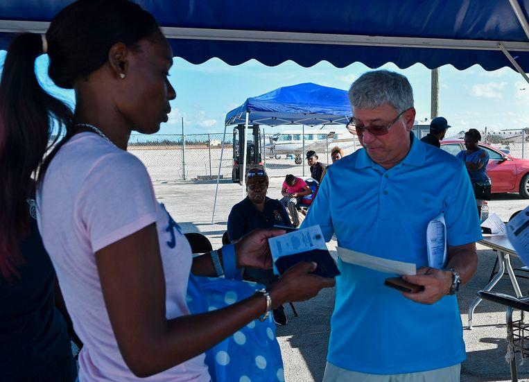 Het paspoort van een vrouw wordt gecheckt op de luchthaven van Freeport om naar Florida te kunnen vliegen. Beeld AFP