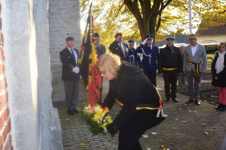 Burgemeester Tania De Jonge legt bloemen neer aan het herdenkingsmonument in Outer.